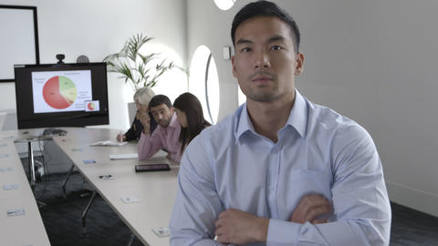 Portrait of businessman with arms crossed while people working in background Footage