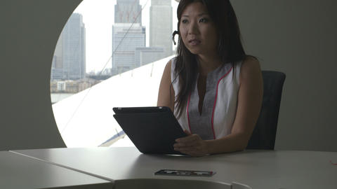 Businesswoman using digital tablet while talking on phone in office Footage