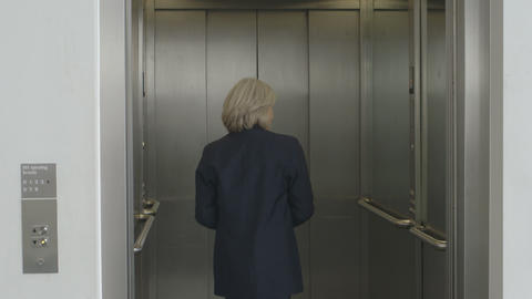 Businesswoman standing in elevator with the door closing Footage