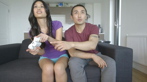 Young couple playing and enjoyment video game in living room Footage