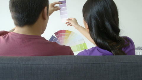 Young couple choosing colour swatch in living room Footage
