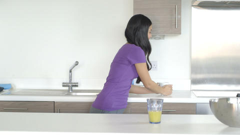 Young woman eating and drinking food in kitchen Footage