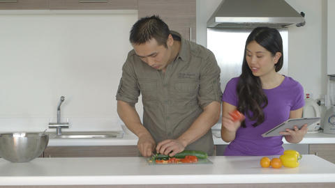 Young couple in kitchen standing and preparing food Footage