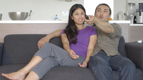 Young couple in kitchen sitting on sofa and watching TV Footage