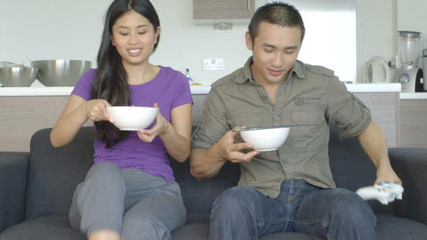 Young couple in kitchen sitting on sofa and eating food Footage