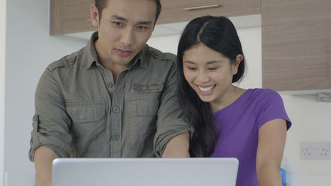 Young couple using laptop in kitchen Footage