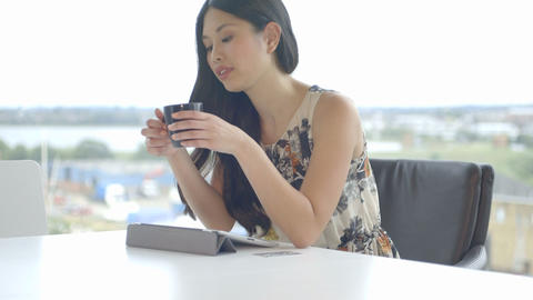 Young woman sitting in office and using digital tablet Footage