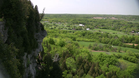 Rocky cliff overlooks the grassy fields and treetops... Stock Video Footage