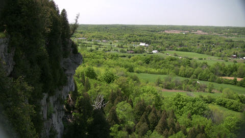 Rocky cliff overlooks the grassy fields and treetops (High Definition) Footage