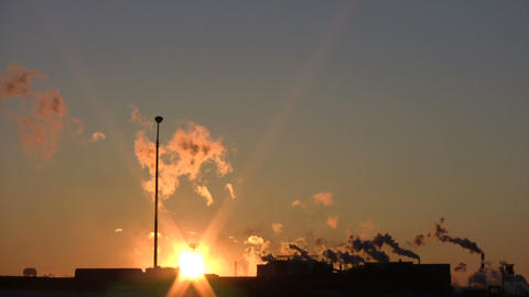 Exhaust from a factory is backlit during sunset (High... Stock Video Footage
