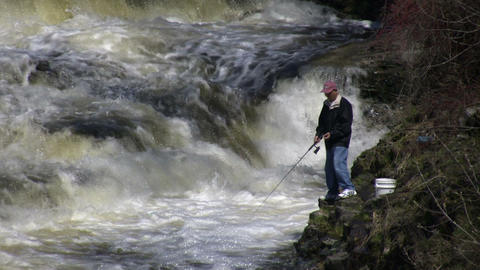 Man is fishing from shore in rough water (High Definition) Stock Video Footage