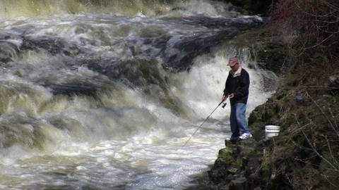 Man is fishing from shore in rough water (High Definition) Footage