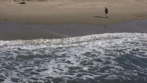 Jogger runs across shore in sunny beach scenic (High... Stock Video Footage