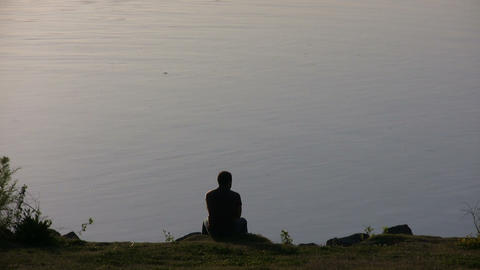 Man is resting on a rock overlooking the Sacramento River Stock Video Footage