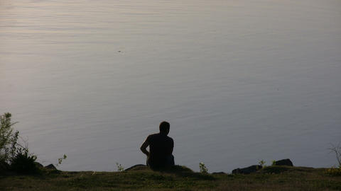 Man is resting on a rock overlooking the Sacramento River Footage