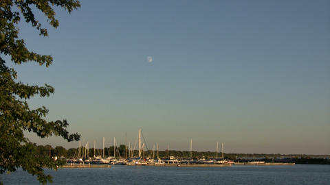 Small marina rests in the distance below moon (High... Stock Video Footage