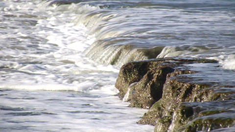 Waves flow over rock formations, creating little waterfalls (High Definition) Footage