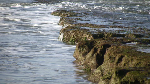 Waves flow over rock formations, creating little... Stock Video Footage