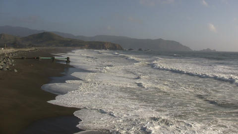 Ocean waves wash up on the sunny San Francisco beach Footage