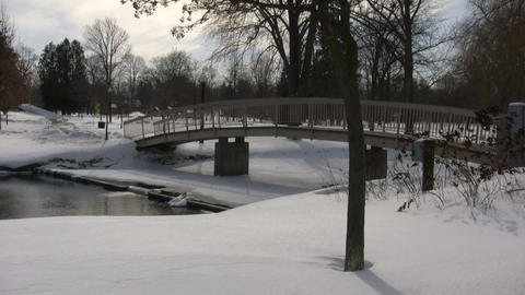 Winter scenic with small bridge crossing over pond (High... Stock Video Footage