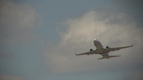 Commercial jet ascending through the cloudy blue sky Stock Video Footage