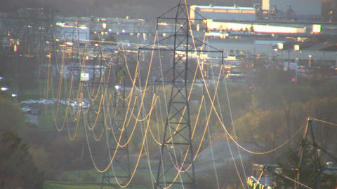 Powerlines hang from many towers admist the sunrise (High... Stock Video Footage
