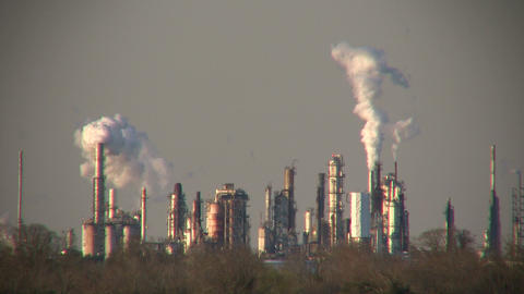 Fumes billow out of large chimneys at Houston BP Refinery Footage