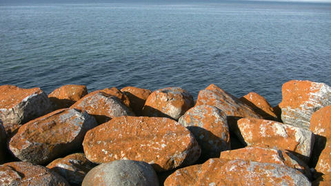 Rusty colored rocks foreground a beautiful ocean view (High Definition) Footage