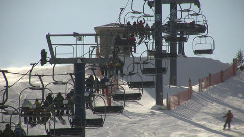 Ski lift slowly transports people to the top (High... Stock Video Footage