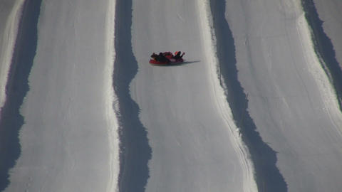 Winter scenic of people tubing down a hill (High Definition) Footage