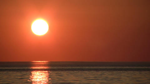Sun hangs low and reflects in the water (High Definition) Footage