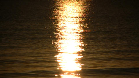 Setting sun is reflected in the rippling water (High Definition) Footage