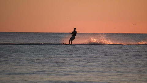 Person is water skiing at sunset (High Definition) Footage