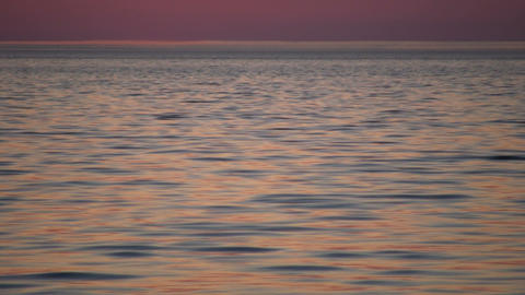 Water's surface reflects the orange sky at dawn (High... Stock Video Footage