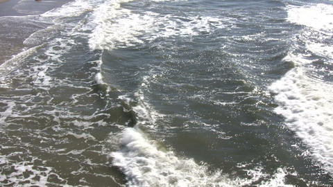 Ocean waves flow towards shore on sunny day (High Definition) Footage