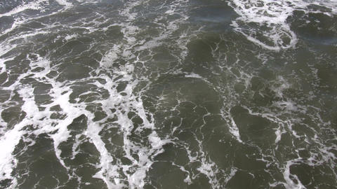 Ocean waves flow towards shore on sunny day (High... Stock Video Footage