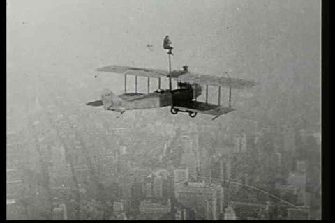 A man climbs a pole attached to a biplane in this  Footage