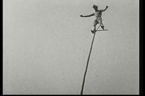 A man balances on a pole at a great height in this Footage