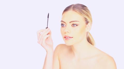 Beautiful woman applying mascara Live Action