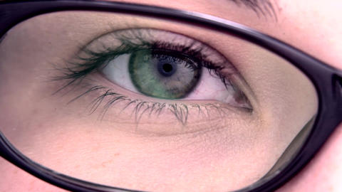 Extreme close up of an eye through the glasses Live Action