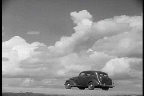 An old car from 1938 drives along a country road a Footage