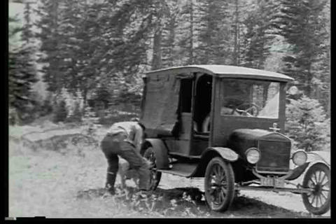 A man loads his dog into an old car in this silent Footage