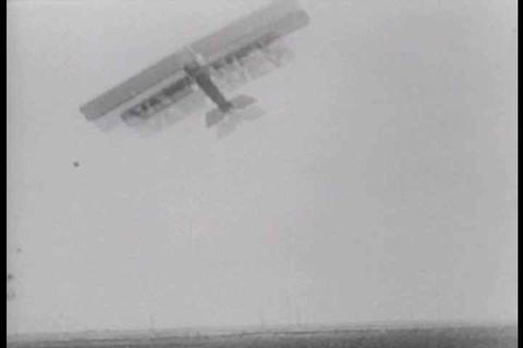 Early aviators walk on the wings of a biplane to d Footage
