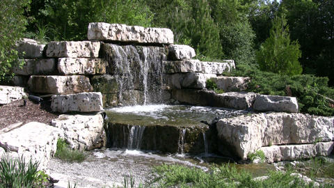 Beautiful garden waterfall splashes into a pond (High... Stock Video Footage