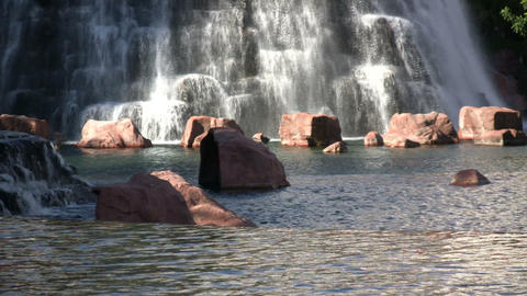 Water flows down rock wall amidst landscaped pond (High Definition) Footage