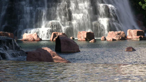 Water flows down rock wall amidst landscaped pond (High... Stock Video Footage