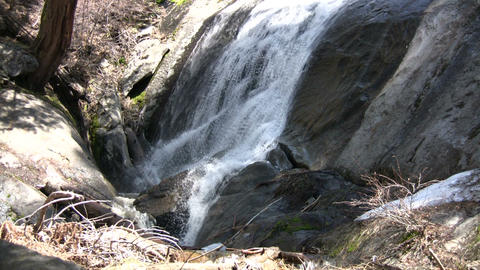 Small waterfall flows down the rocks into a creek Stock Video Footage
