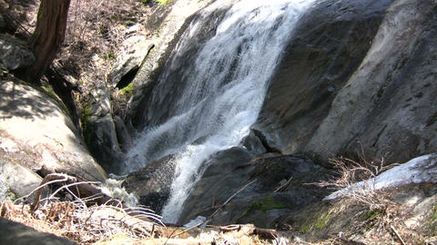 Small waterfall flows down the rocks into a creek Footage