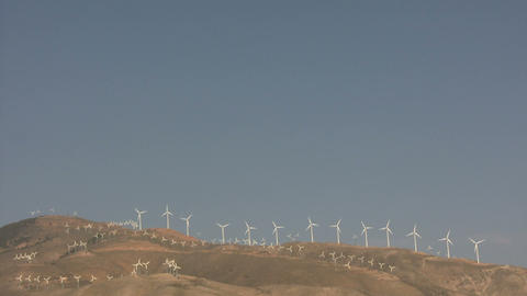 Wind turbines spin in the wind on a sunny day Footage