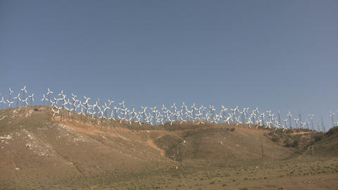 Wind turbines spin in the wind on a sunny day Live Action